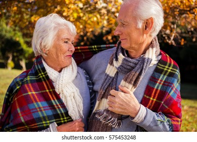 Senior couple embracing with a cover on their shoulder in a park