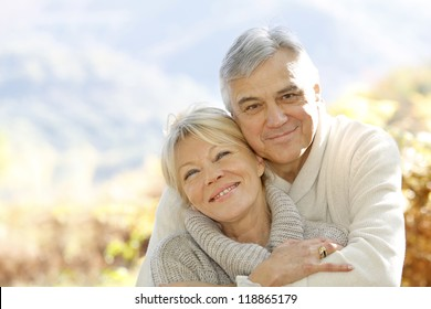 Senior couple embracing each other in countryside
