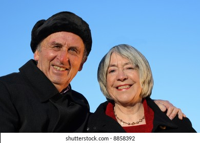 Senior couple embracing and smiling on a blue background.