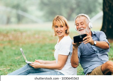 Senior couple enjoy listening to music while sitting on grass in the park