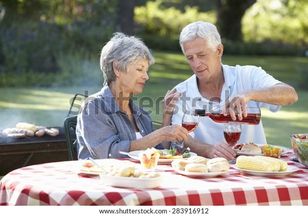 Senior Couple Enjoying Barbeque In Garden Together