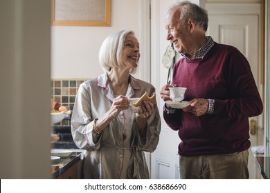 Senior couple are enjoying breakfast and talking  in the kitchen. They are both drinking tea.
