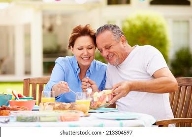 Senior Couple Enjoying Meal In Garden Together