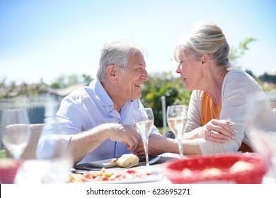 Senior couple enjoying meal in outdoor restaurant