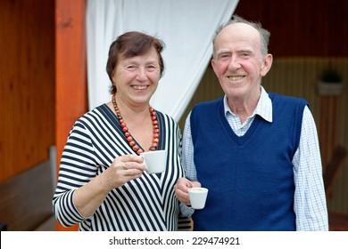 Senior Couple Enjoying Snack At Outdoor Cafe
