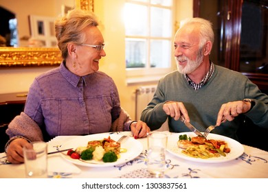 Senior couple enjoying a tasty meal each, while eating healthy foods