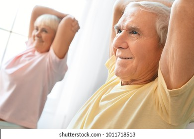 Senior couple exercise together at home health care shoulder stretching