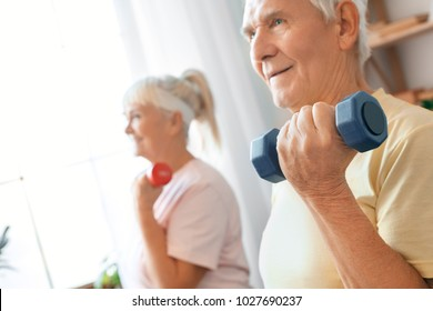 Senior couple exercise together at home health care with dumbbells close-up