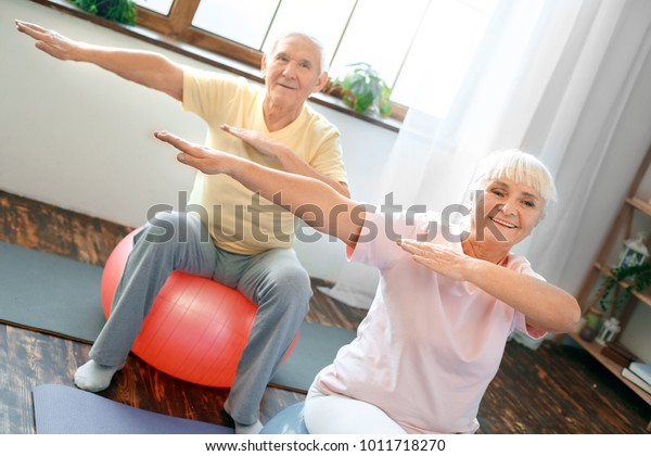 Senior couple exercise together at home doing aerobics hands aside