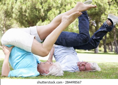 Senior Couple Exercising In Garden Together