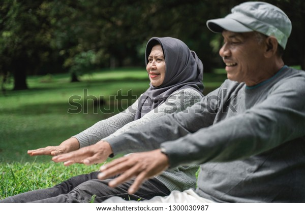 senior couple exercising in nature. two old man and woman doing sport in the park