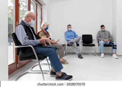 Senior couple with face masks sitting in a waiting room of a hospital together with a young and mature man - focus on the old man in the foreground - Shutterstock ID 1828070570