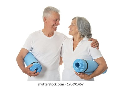 Senior couple with fitness mats On White Background