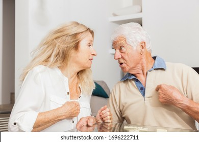Senior couple in full argument. Dispute. Woman and man playing game Dominoes.