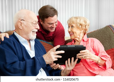Senior couple get a gift of a tablet PC from their adult son.