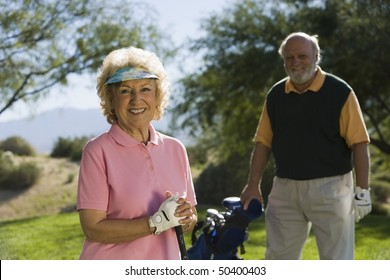 Senior couple in golf course, smiling, focus on woman, (portrait)