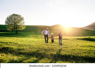 Senior couple with granddaughter on a walk outside in spring nature, jumping.