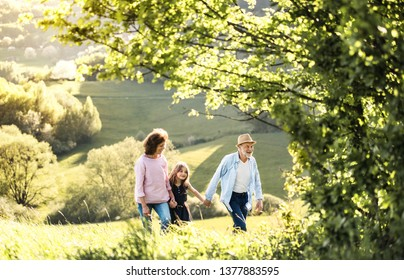Senior couple with granddaughter on a walk outside in spring nature.