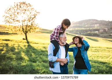 Senior couple with granddaughter outside in spring nature, having fun.