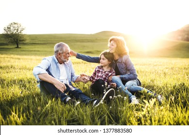 Senior couple with granddaughter outside in spring nature at sunset.