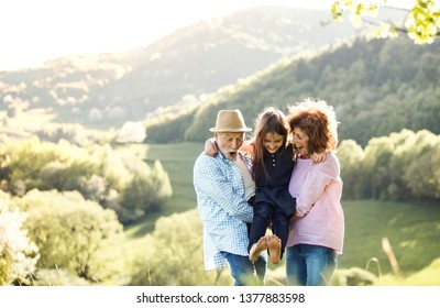 Senior couple with granddaughter outside in spring nature, relaxing and having fun.