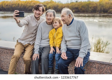 Senior couple with with grandson and great-grandson take a selfie in the autumn park. Great-grandmother, great-grandfather and great-grandson