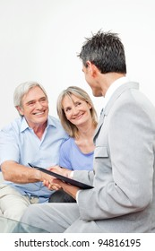Senior couple greeting financial consultant with handshake at home