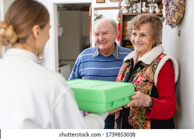 Senior couple greeting volunteer woman delivering a hot meal to their door - Shutterstock ID 1739853038