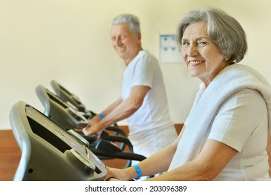 Senior couple in gym on running track