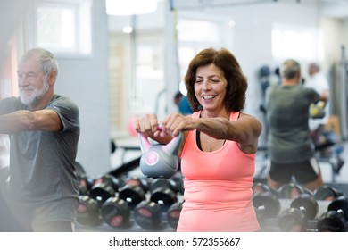 Senior couple in gym working out using kettlebells.