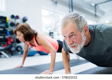 Senior couple in gym working out, doing push ups