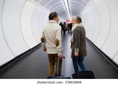 Senior couple in hallway of subway pulling trolley luggage.