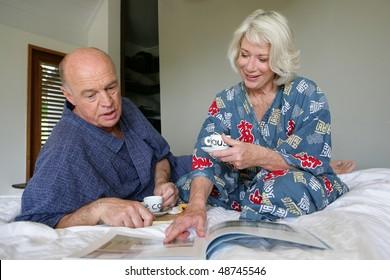 Senior couple having breakfast in bedroom