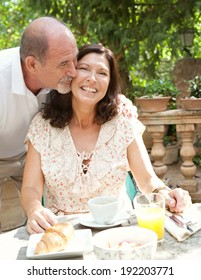 Senior couple having breakfast together at a table in a luxury hotel garden during a holiday. Mature people eating and drinking healthy food enjoying each others company, kissing. Outdoors lifestyle.
