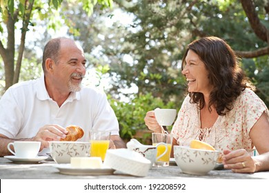 Senior couple having breakfast together at a table in a luxury hotel garden during a sunny day. Mature joyful people eating healthy food and having fun while drinking coffee. Outdoors lifestyle.