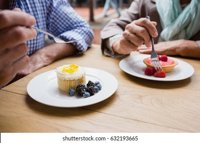 Senior couple having cupcake with blueberries and blackberries in outdoor café