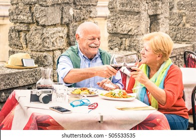 Senior couple having fun eating at restaurant on traveling - Mature man and woman wife on active elderly vacation - Happy retirement concept with retired people together - Warm cloudy day color tones