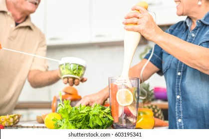 Senior couple having fun in kitchen with healthy food - Retired people cooking at home preparing blended centrifuge smoothie with bio fruit and vegetable - Happy elderly concept with mature pensioner