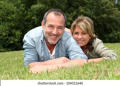 Senior couple having fun laying in grass