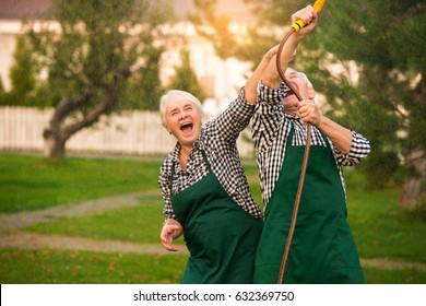 Senior couple having fun outdoors. Cheerful people with water hose. Old and crazy.