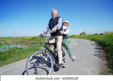 Senior couple having fun riding on the same bike