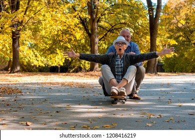 Senior couple having fun together while riding skateboard in autumn park