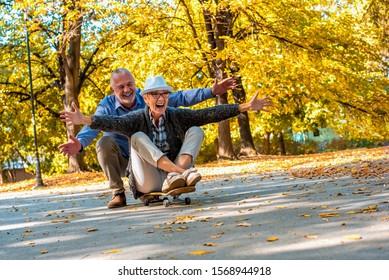 Senior couple having fun together while riding skateboard in autumn park