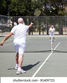 Senior couple having a game on the tennis court.