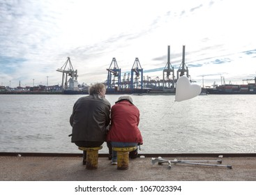Senior couple having love meeting in Hamburg Port. Senior lady holds a balloon in a heart shape. Hamburg, Germany, 11 March 2017