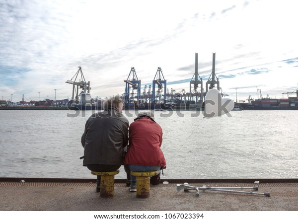 Senior couple having love meeting in Hamburg Port. Senior lady holds a balloon in a heart shape. Hamburg, Germany, 11 March 2017