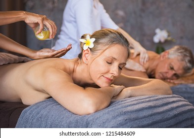 Senior couple having oil ayurveda spa treatment at wellness center. Beautiful mature woman having a back massage with her husband. Relaxed woman and man enjoying a spa beauty treatment.