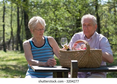 Senior couple having a picnic outside in the park together