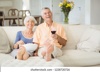 Senior couple having popcorn and glass of wine in living room at home