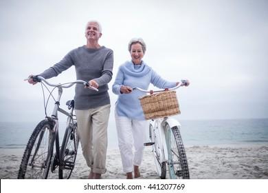 Senior couple having ride with their bike on the beach